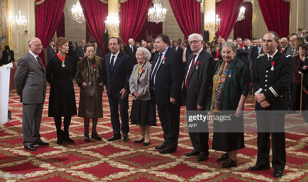 Former European parliament member Frederic Rosmini, director the the Paris national opera Brigitte Lefevre, French author Edmonde Charles-Roux, French President Francois Hollande, former member of the French Resistance Cecile Rol-Tanguy, President of the French confederation of butchers Christian Le Lann, former parliament member Rodolphe Pesce, honorary inspector general of national education Francine Best and deputy director of the firefighters' federation Denis Musson pose after a medal awards ceremony at the Elysee Palace in Paris, on February 20, 2014. APF
