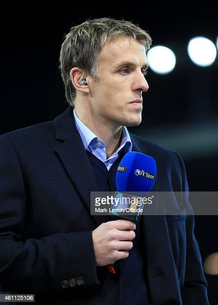 Former Everton player Phil Neville holds the microphone whilst working as a television pundit for BT Sport ahead of the FA Cup Third Round match...