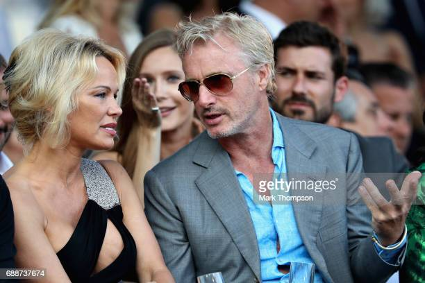 Former F1 driver Eddie Irvine talks with Pamela Anderson at the Amber Lounge fashion show during previews to the Monaco Formula One Grand Prix at...