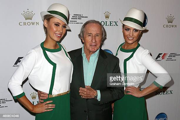 Former F1 World Champion Sir Jackie Stewart poses with two Rolex grid girls during the GP@23 Official Australian Grand Prix Party at Club 23 on March...