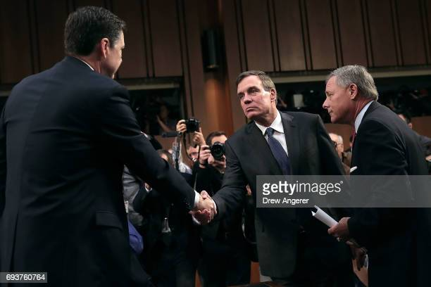 Former FBI Director James Comey is greeted by Senate Intelligence Committee Chairman Richard Burr and ranking member Sen Mark Warner before a hearing...