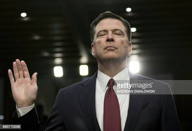 TOPSHOT Former FBI director James Comey is sworn in during a hearing before the Senate Select Committee on Intelligence on Capitol Hill June 8 2017...