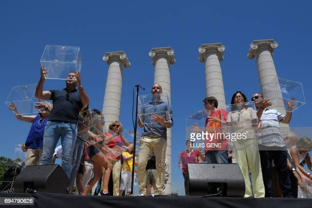 Former FC Barcelona's coach Josep Guardiola holds a electoral urn between by participants during a demonstration dubbed 'Referendum is Democracy'...