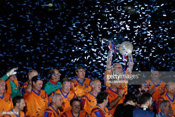 TOPSHOT Former FC Barcelona's goalkeeper Andoni Zubizarreta holds a trophy during a tribute match against SL Benfica at the Camp Nou stadium in...