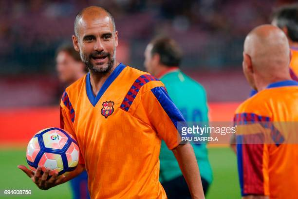 Former FC Barcelona's midfielder Josep Guardiola holds the ball before a tribute match against SL Benfica at the Camp Nou stadium in Barcelona on...