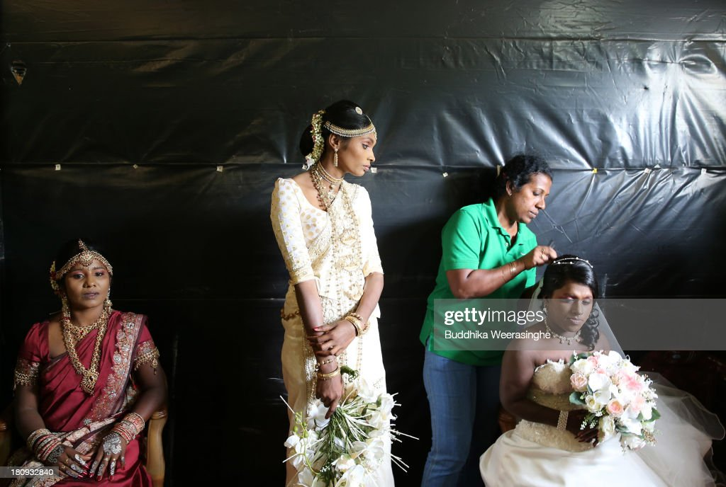Former female Tamil rebel, Premarathnam Suganthini (C), 19 years old, looks over to other former female rebels as they are dressed ahead of a wedding ceremony at the Civil Defence Force military camp on September 18, 2013 in Vishwamadu, Sri Lanka. The former female Tamil rebel and a Sinhalese military officer were legally married today in Sri Lanka's war-torn Northern province. Sri Lanka suffered through a 26-year civil war between the Tamil Tigers and the Sri Lankan military which ended in 2009. On September 21 Sri Lankans of the Northern Province will head to the polls for provincial council elections for the first time since the conflict began.