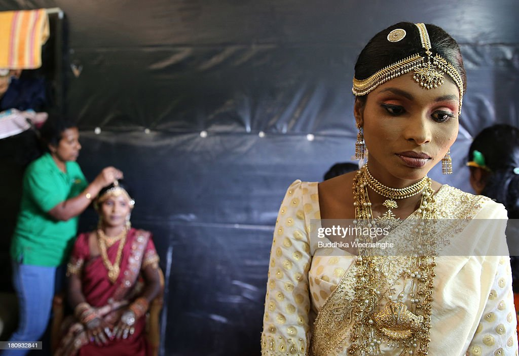 Former female Tamil rebel, Premarathnam Suganthini (R), 19 years old, looks over to another female rebel as they are dressed ahead of a wedding ceremony at the Civil Defence Force military camp on September 18, 2013 in Vishwamadu, Sri Lanka. The former female Tamil rebel and a Sinhalese military officer were legally married today in Sri Lanka's war-torn Northern province. Sri Lanka suffered through a 26-year civil war between the Tamil Tigers and the Sri Lankan military which ended in 2009. On September 21 Sri Lankans of the Northern Province will head to the polls for provincial council elections for the first time since the conflict began.