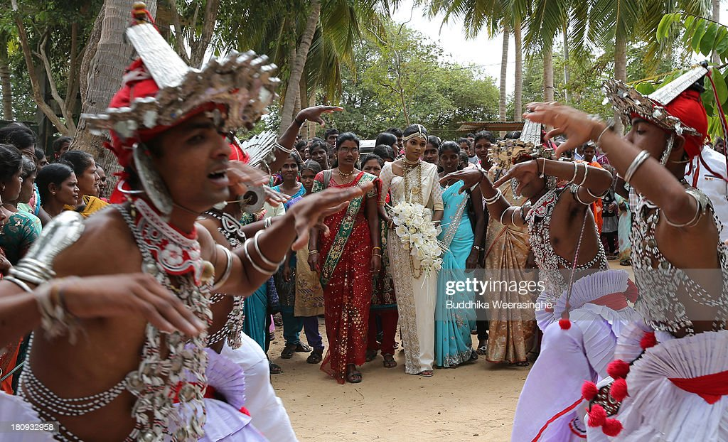 Former female Tamil rebel, Premarathnam Suganthini (C), 19 years old, walks to the 'poruwa ceremony' with her relatives during her wedding ceremony at the Civil Defence Force military camp on September 18, 2013 in Vishwamadu, Sri Lanka. The former female Tamil rebel and a Sinhalese military officer were legally married today in Sri Lanka's war-torn Northern province. Sri Lanka suffered through a 26-year civil war between the Tamil Tigers and the Sri Lankan military which ended in 2009. On September 21 Sri Lankans of the Northern Province will head to the polls for provincial council elections for the first time since the conflict began.