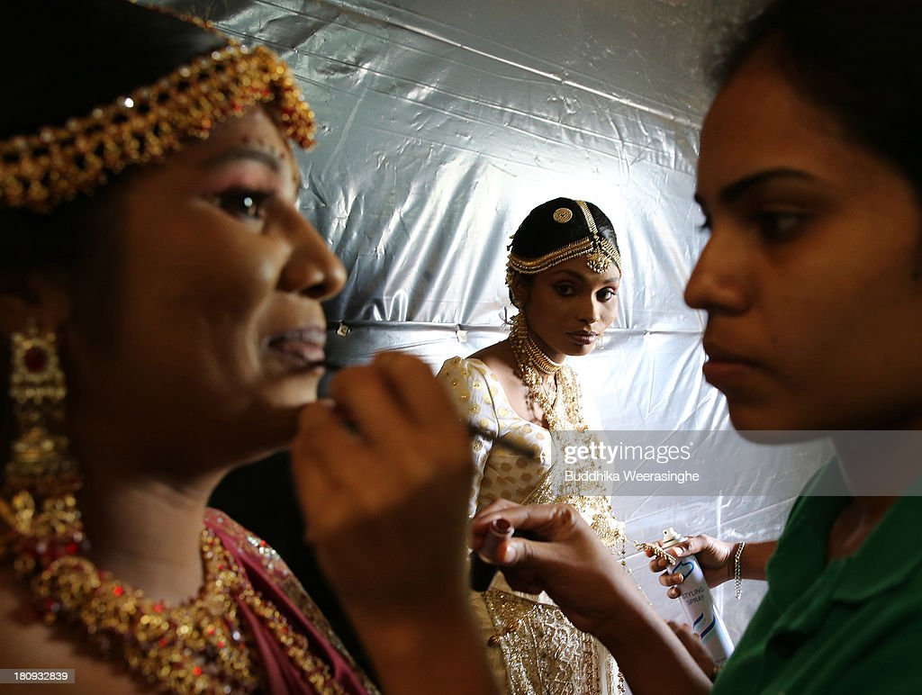 Former female Tamil rebel, Premarathnam Suganthini (C), 19, looks over to another former female rebel as they are dressed ahead of a wedding ceremony at the Civil Defence Force military camp on September 18, 2013 in Vishwamadu, Sri Lanka. The former female Tamil rebel and a Sinhalese military officer were legally married today in Sri Lanka's war-torn Northern province. Sri Lanka suffered through a 26-year civil war between the Tamil Tigers and the Sri Lankan military which ended in 2009. On September 21 Sri Lankans of the Northern Province will head to the polls for provincial council elections for the first time since the conflict began.