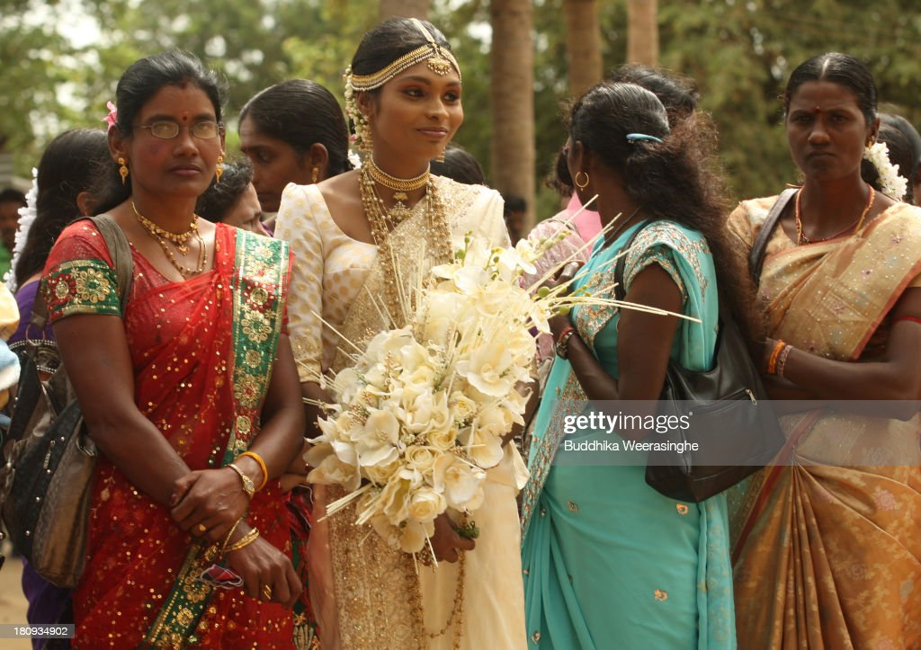 Former female Tamil rebel, Premarathnam Suganthini (C), 19, waits with her relatives to attend the 'poruwa ceremony' during her wedding at the Civil Defence Force military camp on September 18, 2013 in Vishwamadu, Sri Lanka. The former female Tamil rebel and a Sinhalese military officer were legally married today in Sri Lanka's war-torn Northern province. Sri Lanka suffered through a 26-year civil war between the Tamil Tigers and the Sri Lankan military which ended in 2009. On September 21 Sri Lankans of the Northern Province will head to the polls for provincial council elections for the first time since the conflict began.