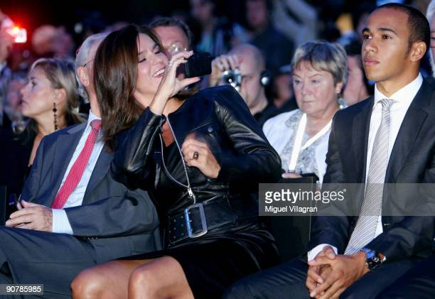 Former figure skating star Katarina Witt takes pictures of the british formula one driver Lewis Hamilton during the MercedesBenz presentation of the...
