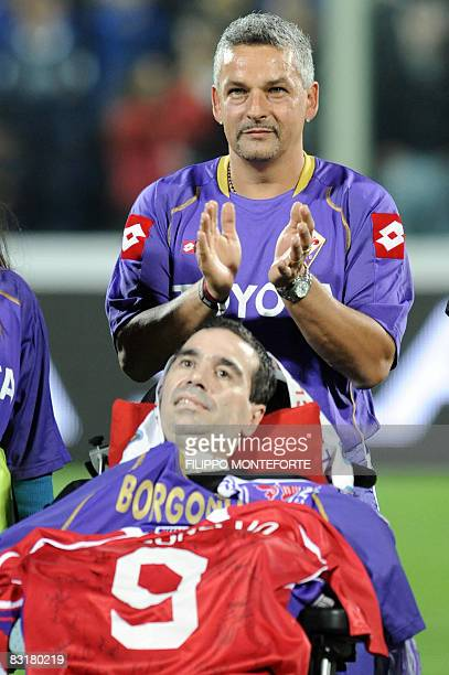 Former Fiorentina's player Roberto Baggio applauds as he stands behind the wheelchair of former teammate Stefano Borgonovo who suffers of Amyotrophic...