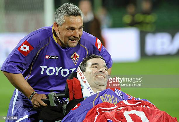 Former Fiorentina's player Roberto Baggio pushes the wheelchair of former teammate Stefano Borgonovo who suffers of Amyotrophic Lateral Sclerosis...