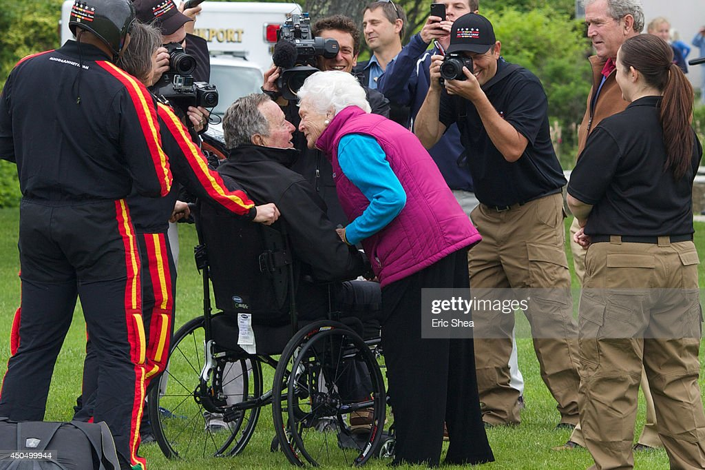 Former first lady Barbara Bush greets her husband and former US President George HW Bush with a kiss after his successful skydive down to St Anne's...