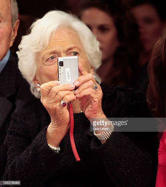 Former First Lady Barbara Bush snaps a few photos during a show by her granddaughterdesigner Laure Bush on day two of Fashion Houston 2010 Presented...