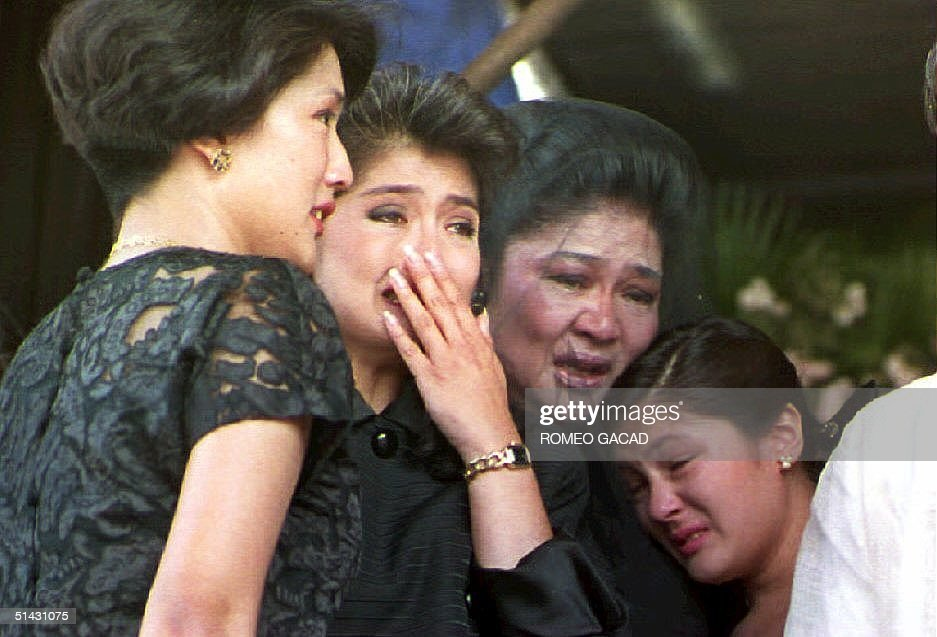 Former first lady Imelda Marcos (2nd R) and her children Irene Araneta (L), Imee Manotoc (C) and adopted daughter Aimee (R) weep 09 September 1993 during a public eulogy for Ferdinand Marcos in Batac, Philippines. Marcos' remains arrived 07 September in his northern Philippine hometown for final burial.