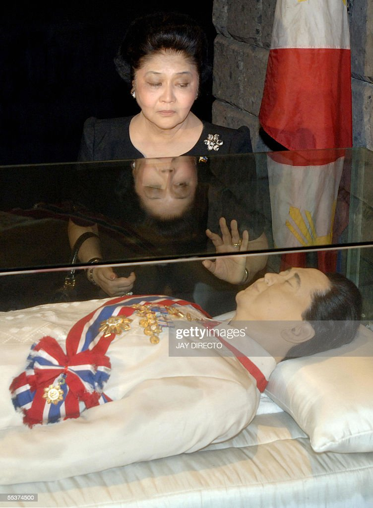 Former first lady Imelda Marcos stands beside a glass case containing the refrigerated remains of her late husband, former Philippines president Ferdinand Marcos, during a visit 11 September 2005 to mark his 88th birthday anniversary. Imelda Marcos supported President Gloria Arroyo during a failed impeachment bid earlier this month, leading to speculation that Arroyo would finally grant the Marcos family's wish to inter the remains of the former president at the National Heroes' Cemetery in Manila. AFP PHOTO/Jay DIRECTO