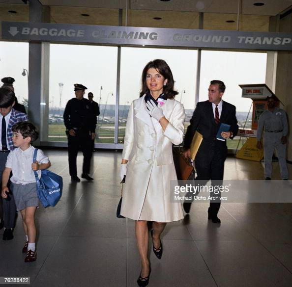 Former First Lady Jacqueline Kennedy and John F Kennedy Jr walk through an airport circa 1966 in Florida