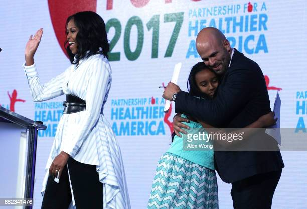 Former First Lady Michelle Obama waves as former White House chef and Senior Policy Advisor for Nutrition Policy Sam Kass hugs Bruktawit Tesfaye...
