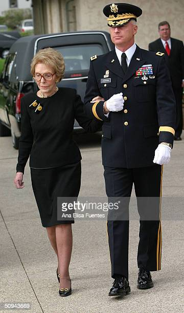 Former first lady Nancy Reagan is escorted by Maj General Galen B Jackman behind the casket of forme president Ronald Reagan as it is placed into a...