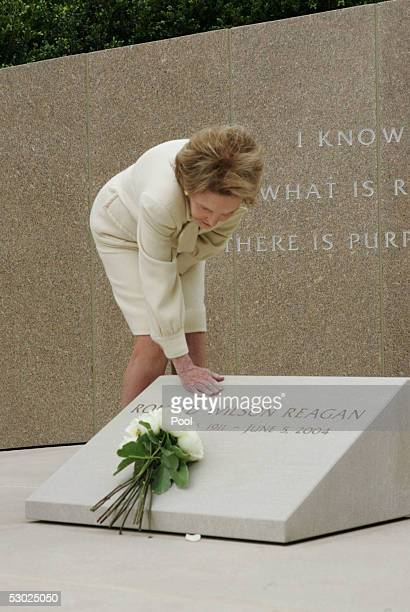 Former first lady Nancy Reagan touches the grave marker of her husband former US President Ronald Reagan after she placed white roses at the site on...