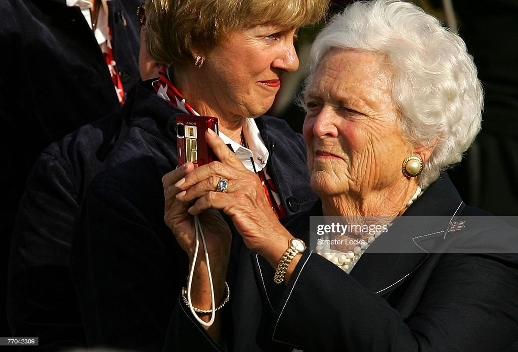 Former First Lady of the United State Barbara Bush shoots pictures as Barbara Nicklaus watches on during the beginning of opening ceremonies prior to...