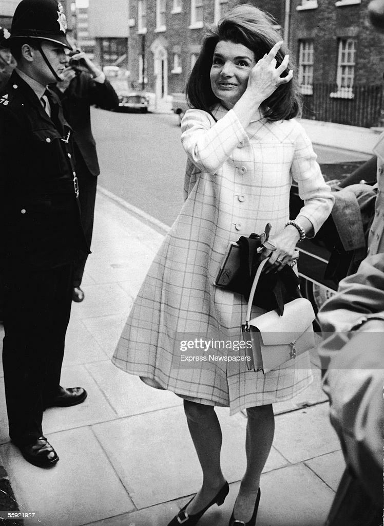Former First Lady of the United States Jacqueline Kennedy (1929 - 1994) smiles as she is photographed fixing her hair, which has been blown out of place by a gusty Spring wind, outside her sister's Westminster home, London, England, April 4, 1966. Mrs. Kennedy flew in from Madrid to visit her sister Lee Radziwill.