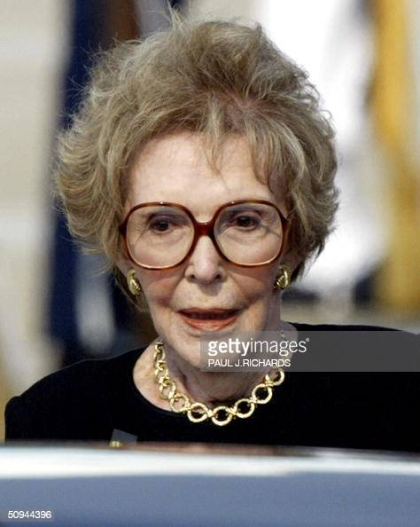 Former First Lady of the US Nancy Reagan pauses before stepping into her limousine as she follows her husband US President Ronald Reagan's flag...