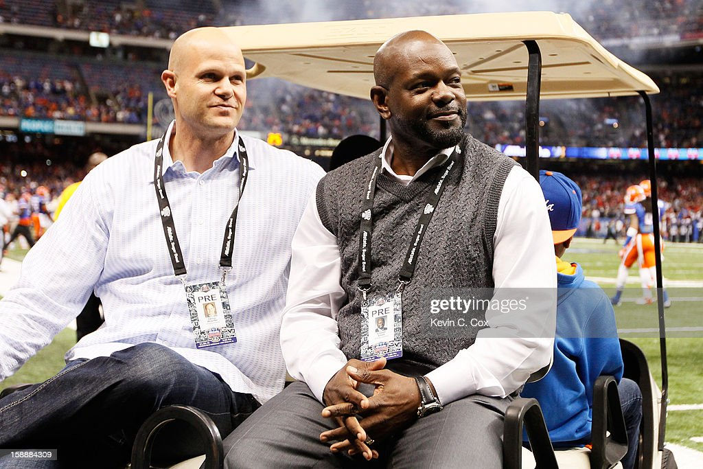 Former Florida Gators stars Emmitt Smith and Danny Wuerffel ride a golf cart onto the field to represent the Gators for the coin toss against the Louisville Cardinals prior to the start of the Allstate Sugar Bowl at Mercedes-Benz Superdome on January 2, 2013 in New Orleans, Louisiana.