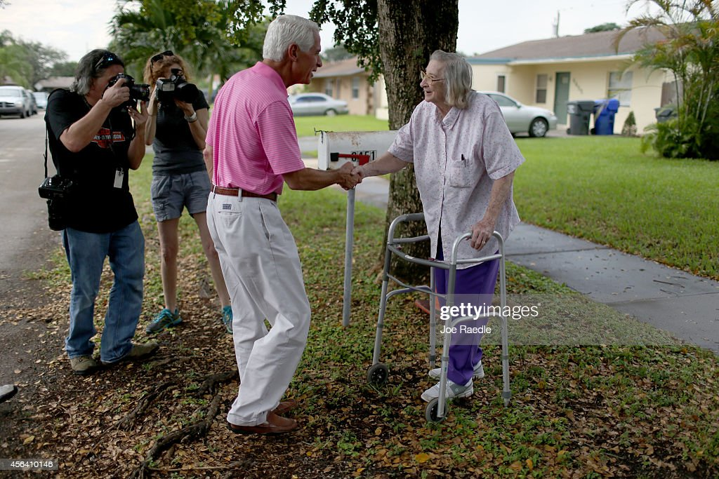Former Florida Governor and current Democratic Party candidate for Governor, <a gi-track='captionPersonalityLinkClicked' href=/galleries/search?phrase=Charlie+Crist&family=editorial&specificpeople=753543 ng-click='$event.stopPropagation()'>Charlie Crist</a> (2nd R) greets Virginia Yzenas after a campaign stop at her neighbors house during his Kitchen Table Tour on September 30, 2014 in Hollywood, Florida. Crist is using the tour to highlight a campaign criticism that middle-class families under Republican Governor Rick Scotts deal with a low-wage, high-cost economy.