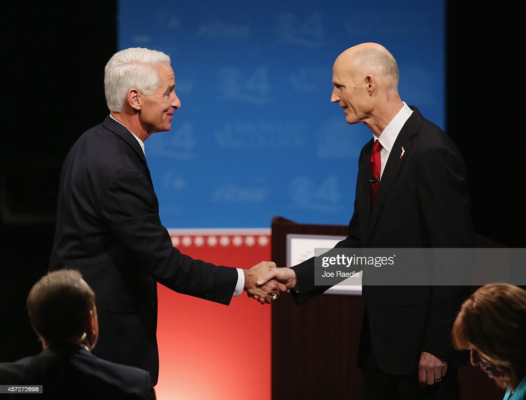 Former Florida Governor and Democratic candidate for Governor <a gi-track='captionPersonalityLinkClicked' href=/galleries/search?phrase=Charlie+Crist&family=editorial&specificpeople=753543 ng-click='$event.stopPropagation()'>Charlie Crist</a> (L) and Republican Florida Governor Rick Scott shake hands after finishing their televised debate at Broward College on October 15, 2014 in Davie, Florida. Governor Scott is facing off against Crist in the November 4, 2014 governors race.