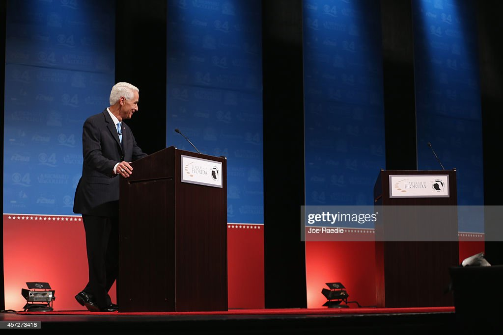 Former Florida Governor and Democratic candidate for Governor Charlie Crist waits next to an empty podium for Republican Florida Governor Rick Scott who delayed his entry onto the stage due to an electric fan that Crist had at his podium as they participate in a televised debate at Broward College on October 15, 2014 in Davie, Florida. Governor Scott is facing off against Crist in the November 4, 2014 governors race.