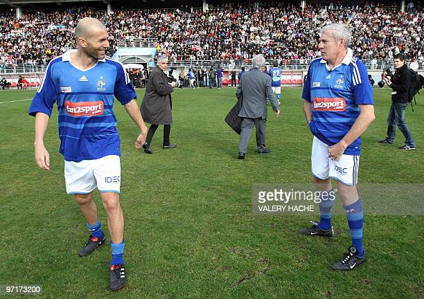 Former football players Luis Fernandes and Zinedine Zidane stand on the pitch before their 'Luis Fernandez jubilee' football match on February 28...