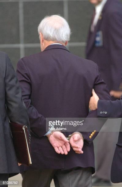 Former Former Enron CEO Kenneth Lay is escorted into federal court by law enforcement officials after being indicted for wire fraud and conspiracy...