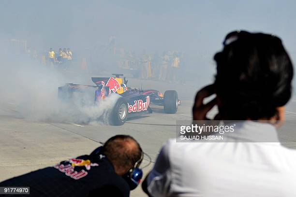 Former Formula One British driver David Coulthard burns rubber on his Red Bull F1 race car over the BandraWorli Sea Link bridge in Mumbai on October...