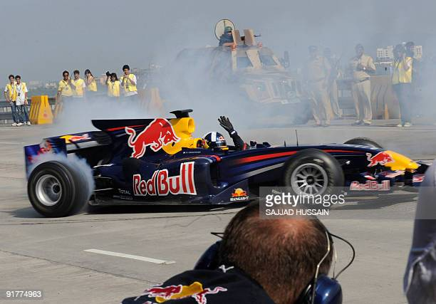 Former Formula One British driver David Coulthard gestures from his Red Bull F1 race car as he burns rubber over the BandraWorli Sea Link bridge in...