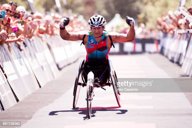 Former Formula One driver and paracyclist Alex Zanardi celebrates as he finishes Ironman 703 Italy race on June 18 2017 in Pescara Italy