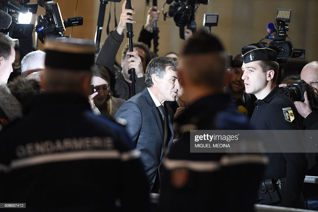 Former French budget minister Jerome Cahuzac surrounded by journalists arrives on the first day of his trial for tax fraud at the courthouse of Paris, on February 8, 2016. Cahuzac, 63, who resigned in disgrace in 2013 after admitting to having a secret Swiss bank account, faces up to seven years in jail and two million euros (USD 2.2 million) in fines if found guilty of stashing offshore his earnings from a lucrative hair-transplant business he ran with his now ex-wife. / AFP / MIGUEL MEDINA