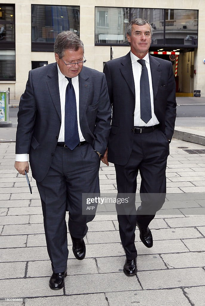 Former French Budget Minister Jerome Cahuzac (R) who resigned from the government in disgrace over an undeclared Swiss bank account, flanked by his lawyer Jean Veil, arrives at the financial pole in Paris, on September 11, 2013.