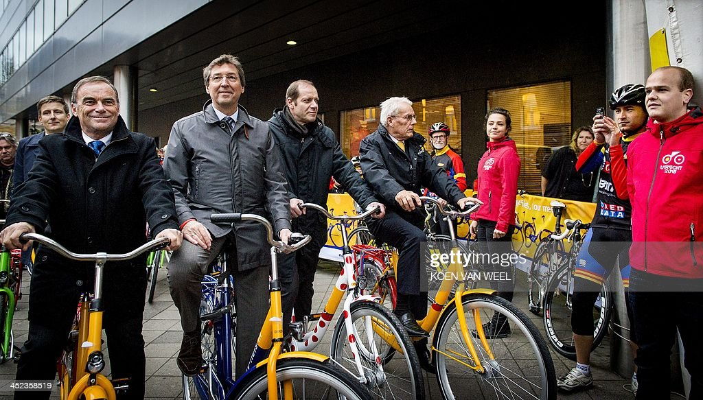 Former French cyclist Bernard Hilnaut, mayor of Utrecht Aleid Wolfsen, Tour de France director Christian Prudhomme and former Dutch cyclist Jan Jansen ride bicycles on their way to a press conference for the official presentation of the 2015 Tour de France opening stage, on November 28, 2013 in Utrecht. Tour de France organisers Amaury Sports Organisation (ASO) revealed today that the opening stage of the Tour de France in 2015 will be an individual time-trial. ** Netherlands out **