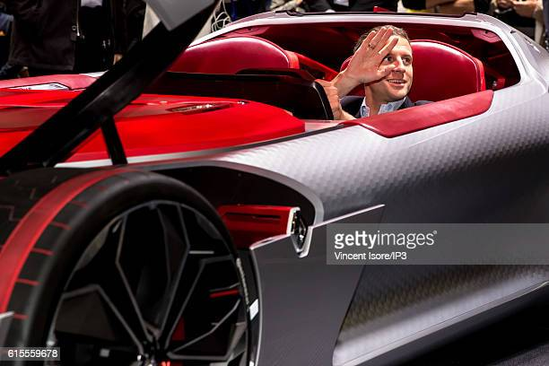 Former French Economy Minister and Founder and Leader of the political movement 'En Marche ' Emmanuel Macron tests a car on the Renault stand during...