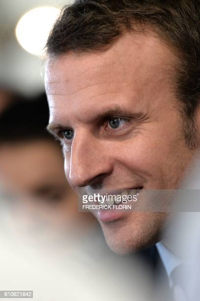 Former French Economy Minister and founder of the political movement 'En Marche' Emmanuel Macron smiles during a visit at the cooking school 'Cuisine...