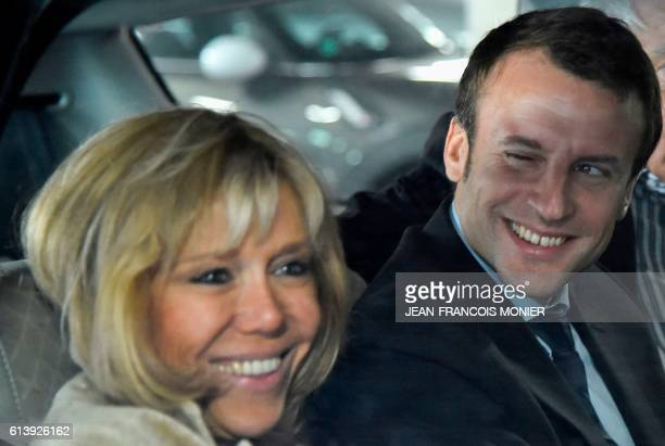 Former French Economy Minister Emmanuel Macron smiles next to his wife Brigitte Macron as they arrive at the station of Le Mans prior to a political...