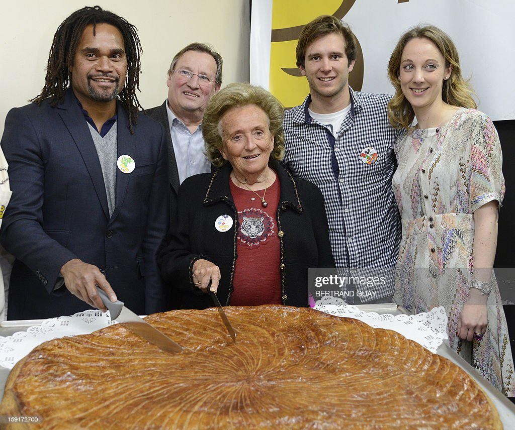 Former French First lady, Bernadette Chirac (C) and the good will ambassador of the 'Pieces Jaunes' (Small Coins) charity campaign's 24th edition, French former football player Christian Karembeu (L) pose before cutting a giant traditional Epiphany cake (galette des rois) beside French swimming Olympic champion Clement Lefert (2ndR) and the General Delegate of the 'Hopitaux de Paris', Danuta Pieter (R), on January 9, 2013 at the Andre Mignot Hospital in Le Chesnay, west of Paris, during the launch of the 'Pieces Jaunes' charity campaign's 24th edition.