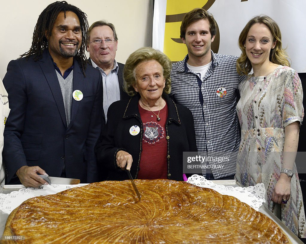 Former French First lady, Bernadette Chirac (C) poses before cutting a giant traditional Epiphany cake (galette des rois) beside the good will ambassador of the 'Pieces Jaunes' (Small Coins) charity campaign's 24th edition, French former football player Christian Karembeu (L), French swimming Olympic champion Clement Lefert (2ndR) and the General Delegate of the 'Hopitaux de Paris', Danuta Pieter (R), on January 9, 2013 at the Andre Mignot Hospital in Le Chesnay, west of Paris, during the launch of the 'Pieces Jaunes' charity campaign's 24th edition. AFP PHOTO BERTRAND GUAY