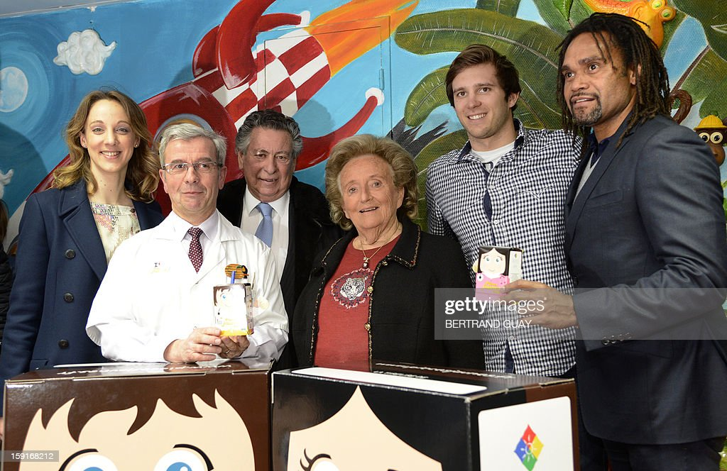 Former French First lady, Bernadette Chirac (C) poses beside doctor Pierre Foucaud (C,L) on January 9, 2013 at the Andre Mignot Hospital in Le Chesnay, west of Paris, during the launch of the 'Pieces Jaunes' (Small Coins) charity campaign's 24th edition. At second rank are pictured the General Delegate of the 'Hopitaux de Paris', Danuta Pieter (L), French swimming Olympic champion Clement Lefert (2ndR) and the good will ambassador of the 'Pieces Jaunes' campaign's 24th edition, French former football player Christian Karembeu (R).