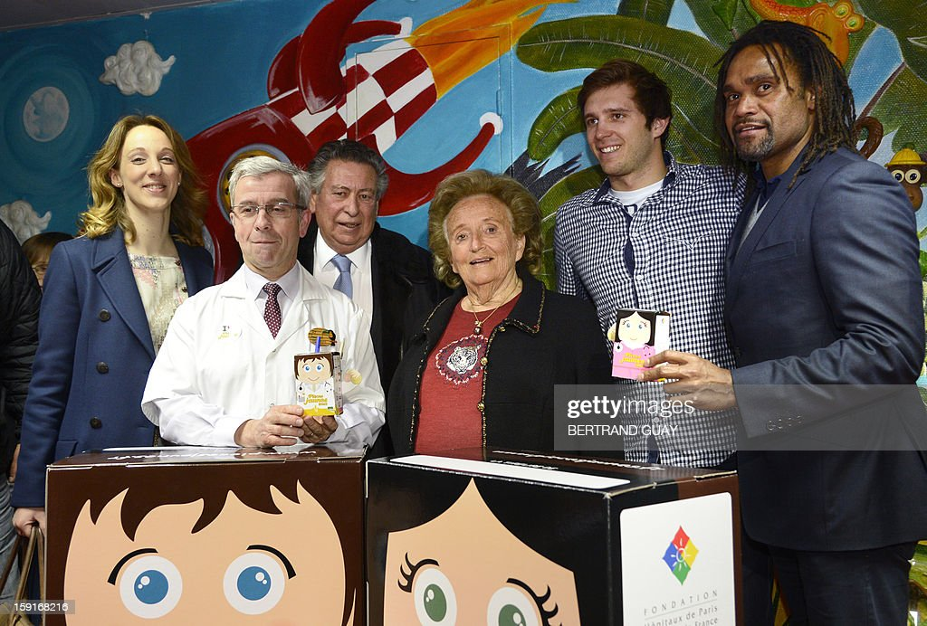 Former French First lady, Bernadette Chirac (C) poses beside doctor Pierre Foucaud (C,L) on January 9, 2013 at the Andre Mignot Hospital in Le Chesnay, west of Paris, during the launch of the 'Pieces Jaunes' (Small Coins) charity campaign's 24th edition. At second rank are pictured the General Delegate of the 'Hopitaux de Paris', Danuta Pieter (L), French swimming Olympic champion Clement Lefert (2ndR) and the good will ambassador of the 'Pieces Jaunes' campaign's 24th edition, French former football player Christian Karembeu (R). AFP PHOTO BERTRAND GUAY