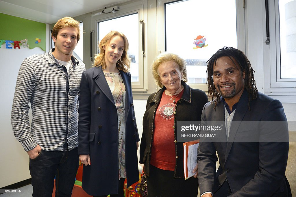 Former French First lady, Bernadette Chirac (C) poses beside the good will ambassador of the 'Pieces Jaunes' campaign's 24th edition, French former football player Christian Karembeu (R) on January 9, 2013 at the Andre Mignot Hospital in Le Chesnay, west of Paris, during the launch of the 'Pieces Jaunes' (Small Coins) charity campaign's 24th edition. From left are pictured French swimming Olympic champion Clement Lefert and the General Delegate of the 'Hopitaux de Paris', Danuta Pieter.