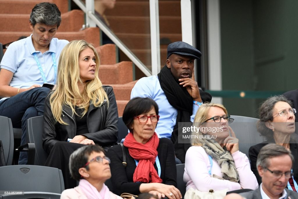 Former French football player Sylvain Wiltord (top R) attends the women's second round match between Hungary's Timea Babos and France's Kristina Mladenovic at the Roland Garros 2016 French Tennis Open in Paris on May 26, 2016. / AFP / MARTIN