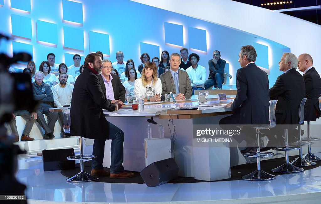 Former French football player turned actor Eric Cantona (L) hosts the TV show 'Le grand journal' on a set of French TV Canal+, on November 22, 2012 in Paris, as part of the launching of French charity association Abbe Pierre Foundation's winter campaign.